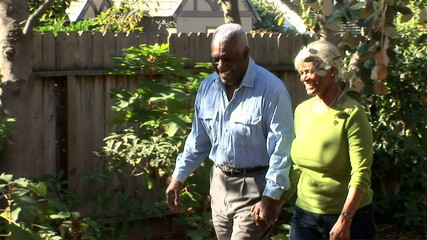 Senior couple walking together through backyard