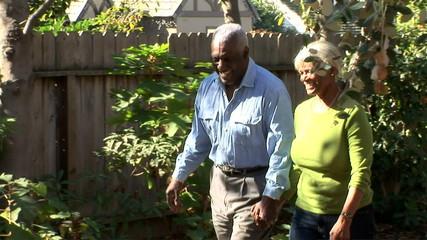 Senior couple walking together through backyard