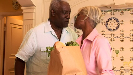 Senior couple bringing home groceries