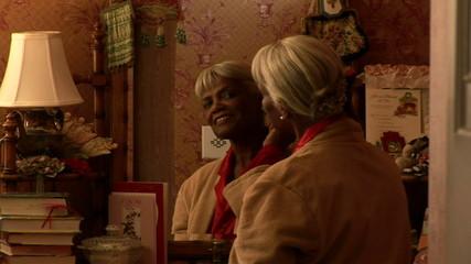 Senior woman combing grey hair by mirror in bedroom