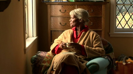 Senior woman drinking tea by bedroom window