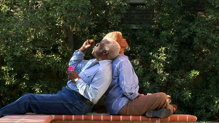 Senior couple blowing bubbles outdoors