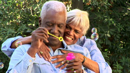 Close up of senior couple blowing bubbles outdoors