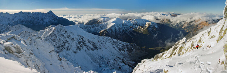 Panorama of snowy peaks and climbing tourists
