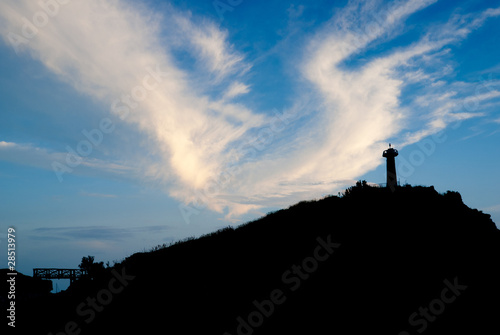 lighthouse silhouette at sunset with dramatic cloud