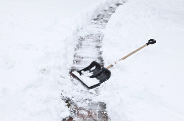 black shovel to remove the snow from the garden path.
