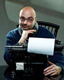 Old fashioned bald writer in glasses writing book