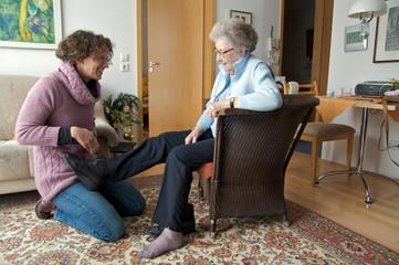 junge Frau hilft Seniorin
