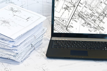 Laptop and stack of project drawings. Working place.