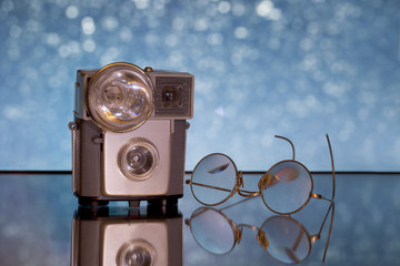 Old camera with flash bulb and antique glasses