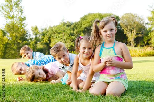Cheerful preschoolers team sitting in the park