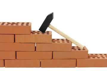 backsteinmauer mit hammer