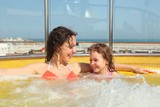 woman with her daughter both smiling in hot tub on cruise ship.