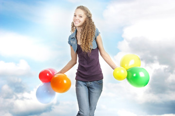 young happy teen girl with balloons on sky background