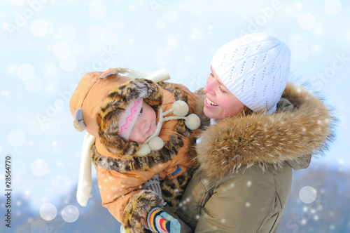 Happy young mother and her daughter in winter