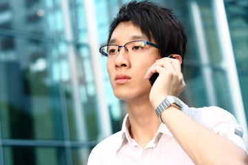 casual asian businessman talking on his cell phone