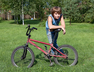 The teenager costs on a solar lawn and leans against a bicycle.