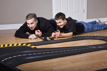Father And Son Playing With Racetrack
