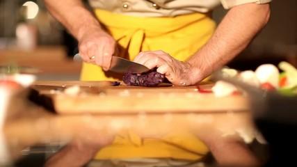 Profi Koch schneidet eine vitelotte Kartoffel