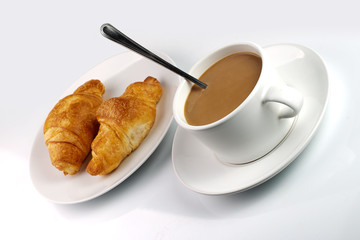 white coffee mug and croissants on plate