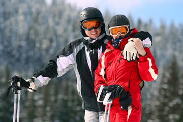 Portrait of smiling couple on skis in the mountains