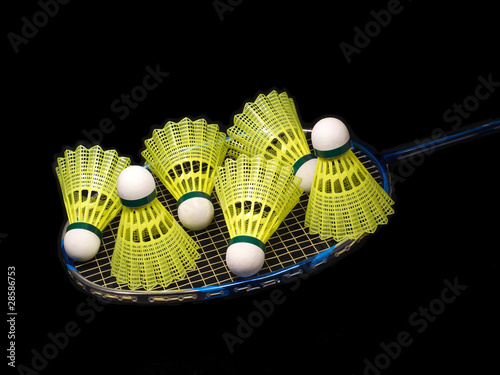 Badminton racket wit six yellow shuttlecock isolated on black