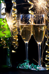 Bottle of champagne, two glasses, ribbons and sparklers.