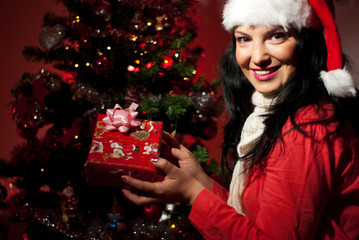 Cheerful woman holding Christmas gift