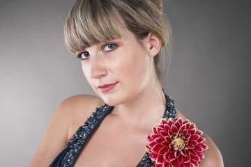 Close-up portrait of beautiful young woman with flower