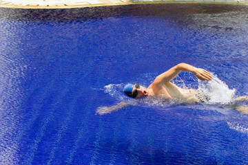 The young sports swimmer in pool