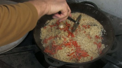 Stirring pilaf with spoon, removing garlic from Cauldron