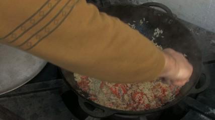 Stirring pilaf with big spoon in Cauldron