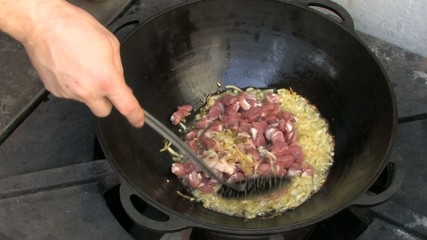 Stirring pieces of meat and Frying onion in Wok
