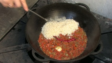 Adding Rice to Pilaf ingredients in Wok