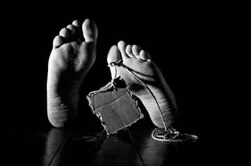 Death. Feet of a corpse on a wooden floor with cardboard