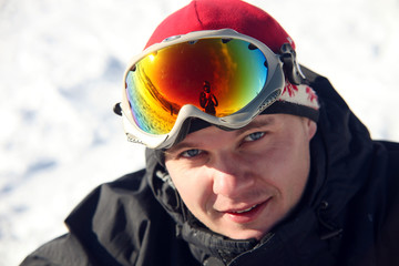 Close-up portrait of snowboarder sitting on snow