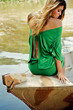 beautiful blond model sitting on boat wearing green dress