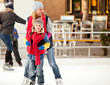 a mother helps her son learn to ice-skate