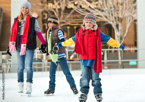 a family skates together at an ice rink