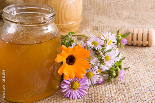 honeycomb, flowers and honey in glass on sack