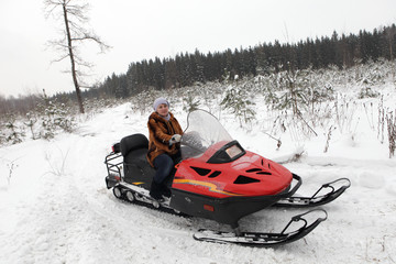 Woman is posing on snowmobile