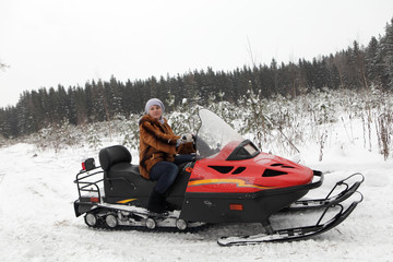 Woman on red snowmobile