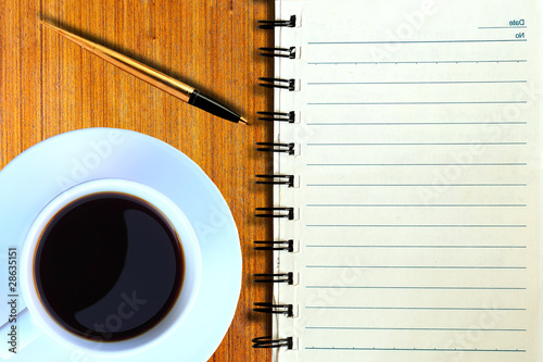 Coffee cup, spiral notebook and pen on the wooden table .