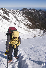 Lone male mountain climber climbing a snowy ridge