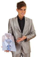 smiling young man in grey suit presenting shirts