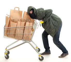 thief in  balaclava with shopping cart with papers bags