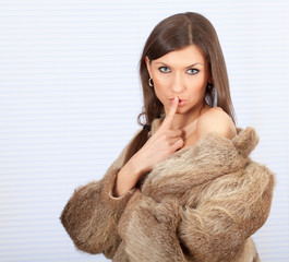 young woman in a fur coat, keeping silence