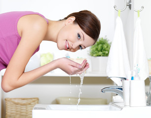 Woman washing her face by water