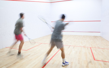 Squash players in action on a squash court (motion blurred image