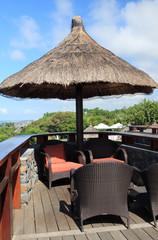 salon extérieur sur terrasse sous parasol de paille